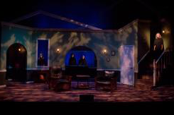 The set of a theater performance. The setting is the interior of a house with young women dressed in black staring out of the windows and another young lady standing in the stairwell.