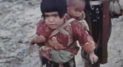 A small girl carrying wh在 seems to be her baby brother on her back.