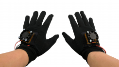 Black gloves with electronics (peltier device, raspberry pi, etc.) on them.
