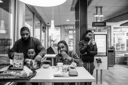 Roland Whitley sits with his son 和 two mentees at a McDonalds in a photo that was part of a series that won the 2019 Dorothea Lange Fellowship